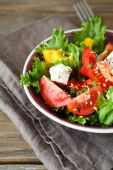 Salad with tomatoes, cheese and greens in a bowl on napkin — Foto de Stock