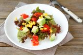Salad with avocado, tomatoes and corn on a white plate — Stock Photo