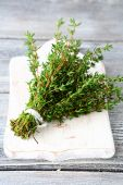 Fragrant thyme on a white chopping board — Stock Photo