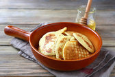 Nutritious pancakes with honey on a ceramic pan — Stock Photo