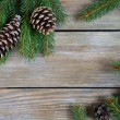 Christmas pine branch with cones on boards — Stock Photo #56477965