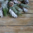 Xmas fir branch with cones on wooden boards — Stock Photo #56477985