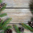 Xmas frame with green pine branch with cones on boards — Foto Stock #56479613