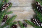 Vánoční rám s zelených borových větví s kužely na desky — Stock fotografie