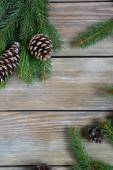 Christmas pine branch with cones on boards — Stock Photo
