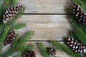 Xmas frame with green pine branch with cones on boards — Stock Photo