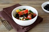 Salad with tomatoes, olives and cheese in a white bowl — Stock Photo