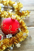 Christmas balls with tinsel on a wooden boards — Stock Photo