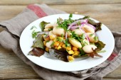 Tasty salad with beans, lettuce, onions and corn on a plate — Stock Photo