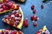 Slices of tart with raspberries on a slate background — Stock Photo