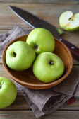 Nutritious green apple in a clay bowl — Stock Photo