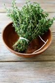 Fresh thyme in a bowl on wooden boards — Stock Photo