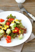Summer salad with avocado, tomatoes and corn on a plate — Stock Photo