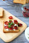 Bruschetta with sun-dried tomatoes on the board — Stock Photo