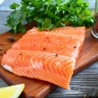 Raw fillet Salmon with greens and lemon on a board — Stock Photo #58848629