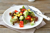 Nutritious salad with avocado, tomatoes and corn on a plate — Stock Photo