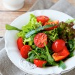 Fresh salad with tomatoes and arugula on a plate — Stock Photo #59582481
