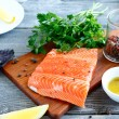 Fillet Salmon with fresh herbs and lemon on a board — Stock Photo #61442405
