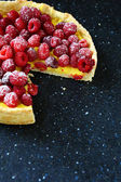 Delicious pie with raspberries dusted powdered sugar — Stock Photo