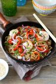 Chinese buckwheat noodles with spicy shrimp in a frying pan — Stock Photo