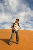 Woman tourist climbing a sand dune — Stock Photo