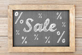 Sale chalk writing with percentage signs on chalkboard — Stock fotografie