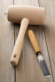 Wooden mallet and chisel on wooden table — Stock Photo