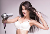 Brunette woman with hairdryer. — Stock Photo
