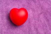 Red heart on purple cloth background — Stock Photo