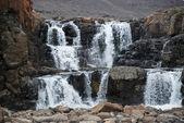 Paisagem com rochas e uma cachoeira. — Fotografia Stock