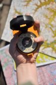 Compass in hand on a blurred background topographic maps. — Stock Photo