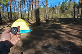 Compass in the forest on the background of the tent. — Foto de Stock