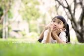 Aziatische jong geitje denken tijdens het spelen in de tuin — Stockfoto