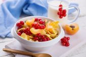 Cornflakes in bowl with red currant — Stock Photo