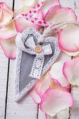 Decorative heart on rose petals — Stock Photo
