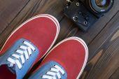 Vecchie macchina fotografica e pattini rossi su un tavolo in legno — Foto Stock