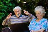 Elderly couple having fun with the laptop outdoors — Stock Photo