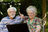 Elderly couple having fun with the laptop outdoors — Foto de Stock