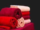 Stack of colorful terry towels on a shelf — Stock Photo
