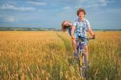 Portrait of a teen on a bicycle traveling in rye field — Stock Photo