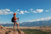 Pretty young woman tourist standing on top of mountain  — Stock Photo