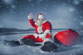Santa Claus sitting in the snow with a laptop and looking away f — Stock Photo
