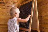 小男孩在黑板上用粉笔绘制 — 图库照片