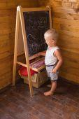 Niño dibujar con tiza en una pizarra — Foto de Stock