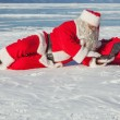 Santa Claus lying on the snow, looking at laptop news — Stock Photo #54233803