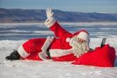 Santa Claus lying on the snow, looking at laptop news — Stock Photo