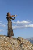 Girl in concert dress, playing the violin, standing on top of a  — Stockfoto