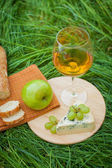 Still life with white wine, baguette, cheese, grape and apple  — Stock Photo