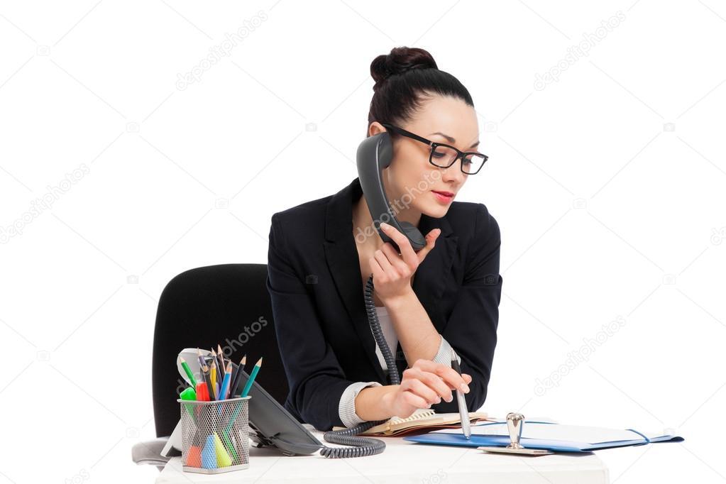 Secretaria morena hablando por tel fono sentado en mesa for La oficina telefono