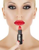 Model on white background applying red lipstick — Stock Photo
